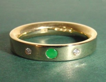 a 9ct yellow gold eternity ring with a central emerald flanked by 2 si quality diamonds