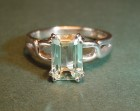 white gold ring with an emerald cut aquamarine with celtic shoulder-work