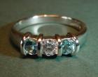 simple platinum engagement ring with central diamond and aquamarines