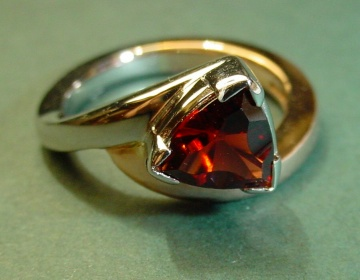 asymmetrical engagement ring in 9ct rose and white gold with a trillion cut garnet