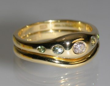 flush engagement ring with diamond, green sapphires and tourmalines