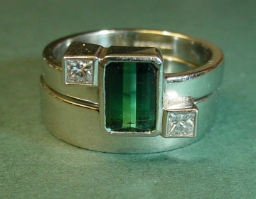 platinum art deco engagement ring with a green tourmaline and diamonds plus a matching wedding ring