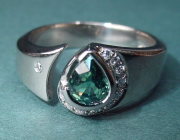 18ct white gold engagement ring with 0.70ct deep green sapphire and 11 h si diamonds