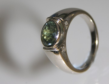 18ct white gold engagement ring with a chequerboard cut green sapphire