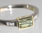 white and yellow gold ring with unusually cut green sapphire and diamonds