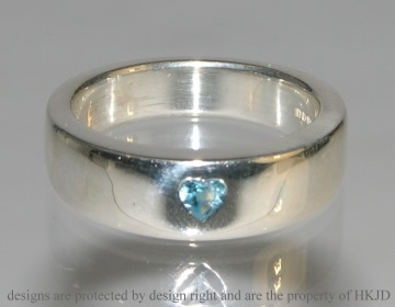 silver dress ring with a heart shaped swiss blue topaz