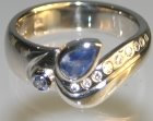 18ct white gold ring with pear shaped .44ct sapphire with 11 brilliant cut diamonds and a 2mm pale blue sapphire
