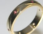 bespoke 9ct yellow gold eternity ring with an engraved wave and rubies