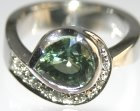 platinum engagement ring with a green sapphire and diamonds