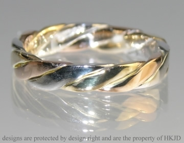 A 9ct three colour gold Celtic twist wedding band