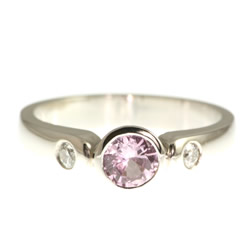 18ct white gold engagement ring with a central pink sapphire and side diamonds