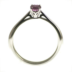 an 18ct white gold and deep pink sapphire solitaire engagement ring