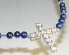 a stone set cross pendant withblue river pearls and swarovski crystals