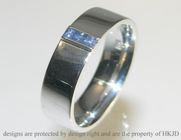 rhodium plated 9ct white gold ring with channel set mid blue sapphires