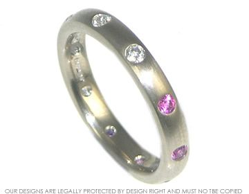 18ct white gold eternity ring with diamonds on one side and pink sapphires on the other