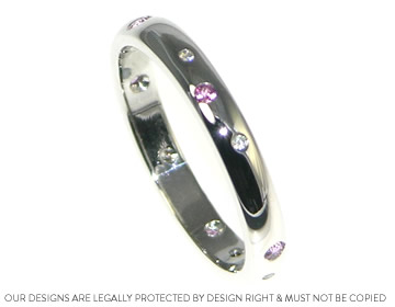 an eternity ring scatter set with diamonds and pink sapphires