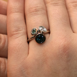 a modern 'cluster' engagement ring with palladium, diamond and tourmalines
