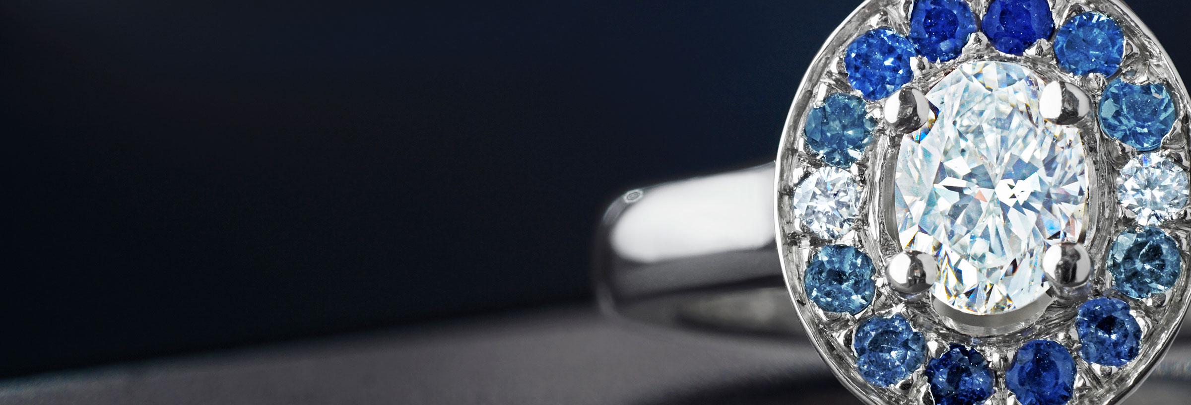 0.61ct oval diamond, graduated sapphire and aquamarine ring