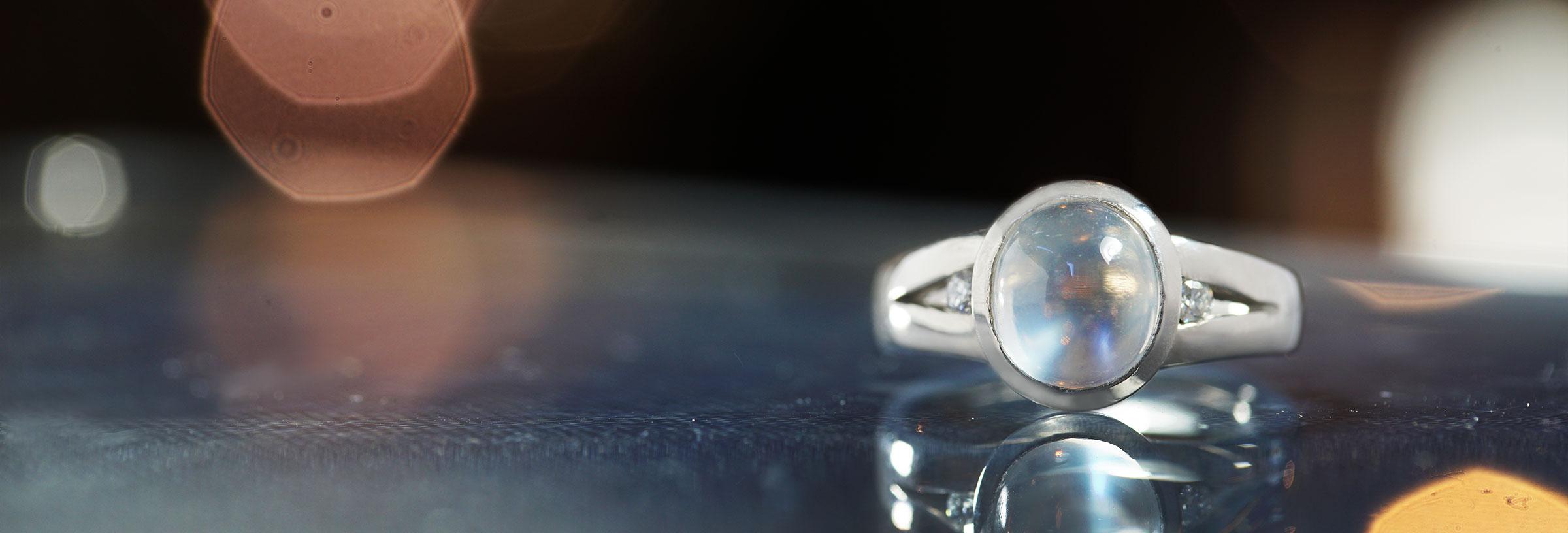 palladium-cabochon-cut-moonstone-and-diamond-split-shoulder-engagement-ring