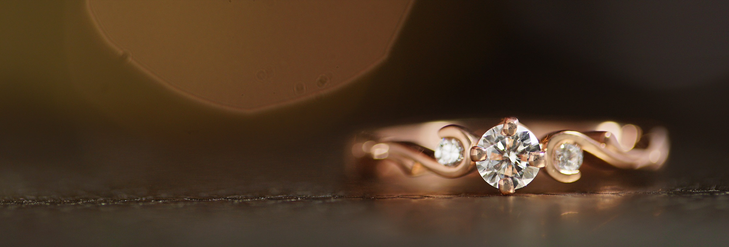 rose-gold-trilogy-style-engagement-ring-with-curl-detail