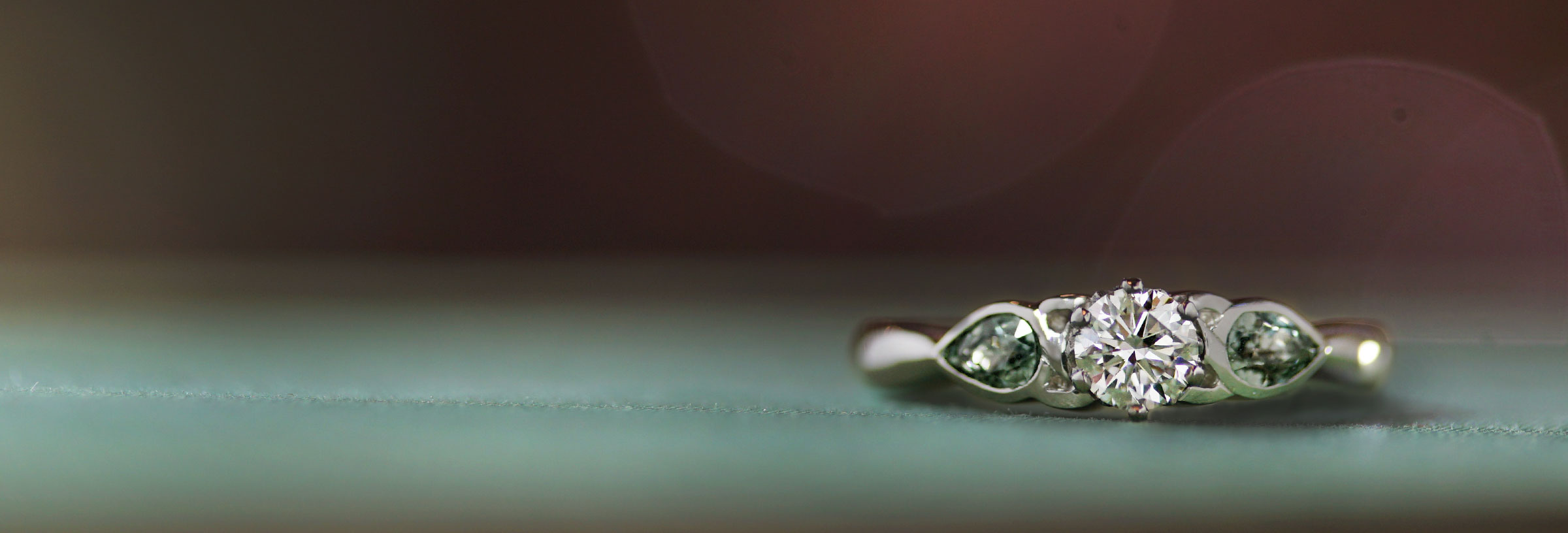 platinum-trilogy-engagement-ring-with-diamond-and-green-sapphires