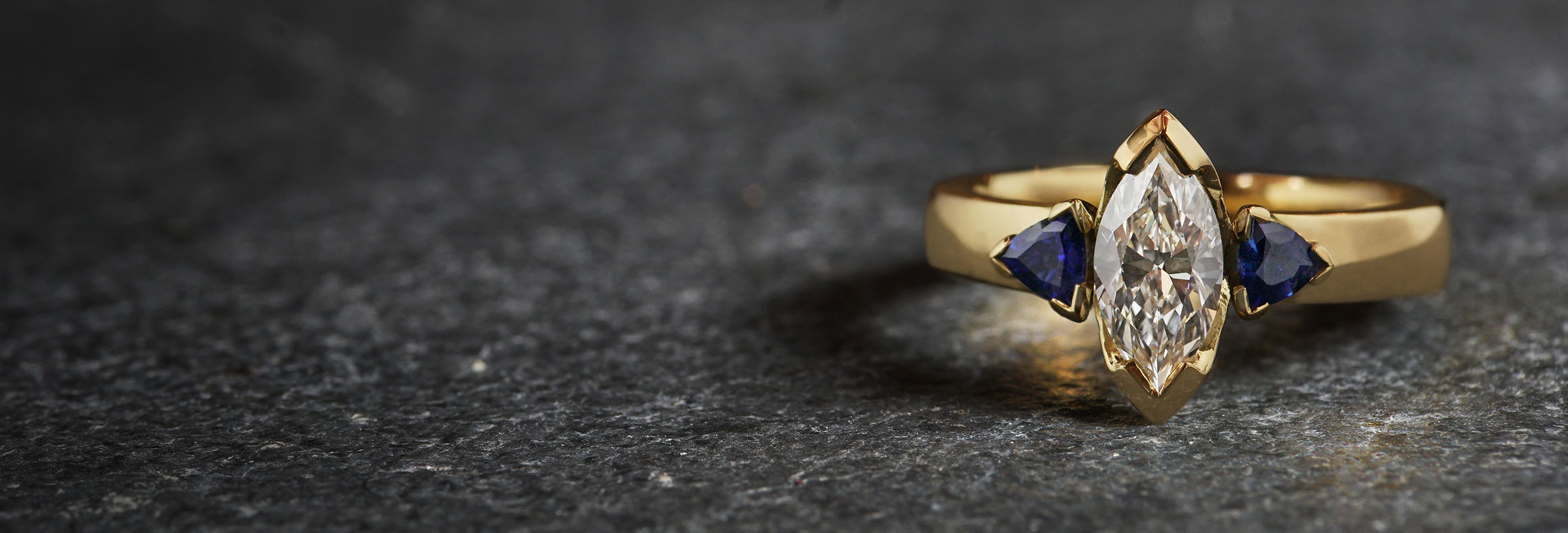 yellow-gold-marquise-diamond-and-trilliant-sapphire-trilogy-engagement-ring